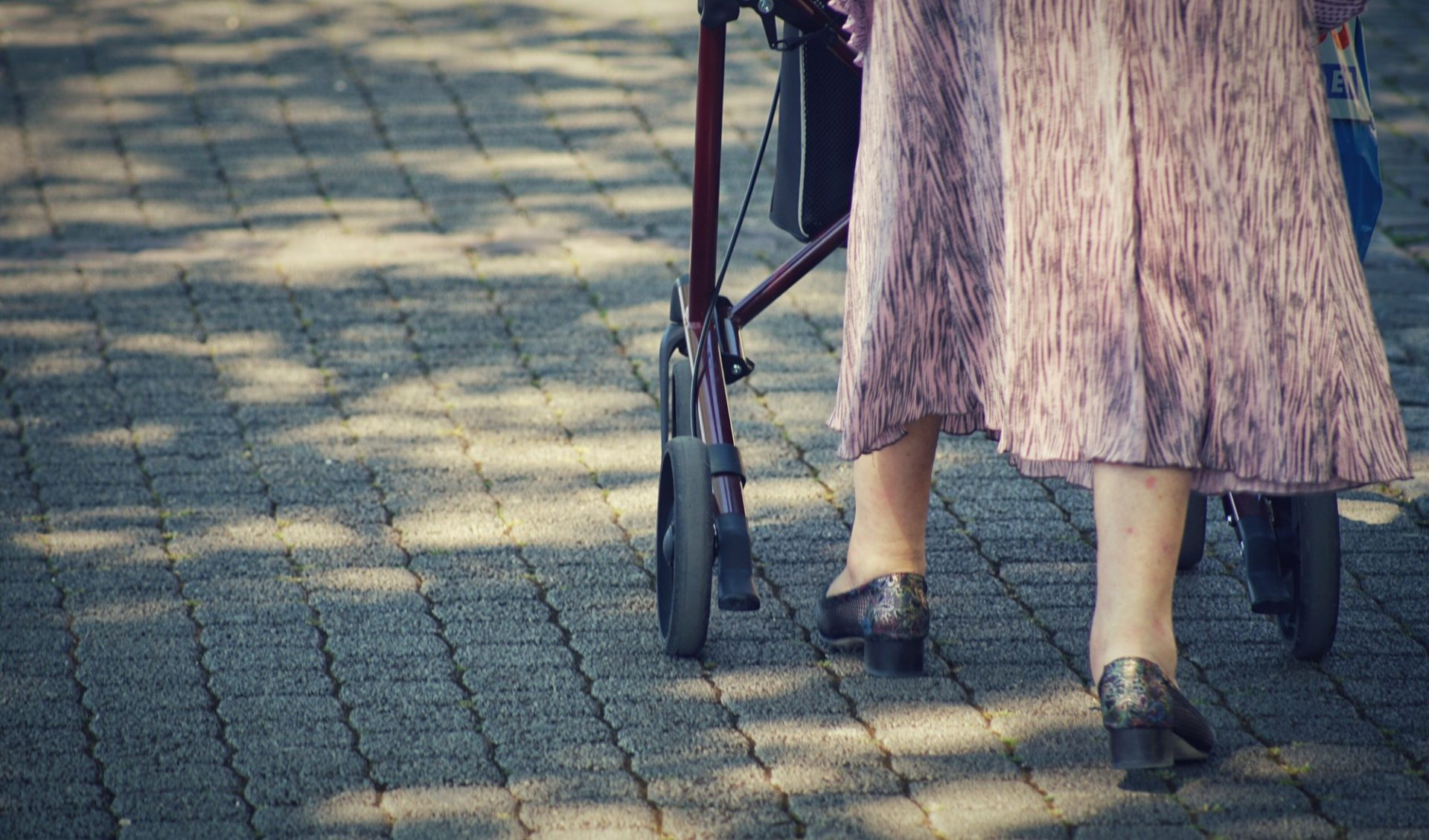 An elderly lady walking outside with a walker