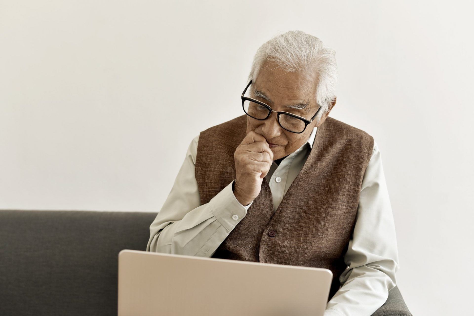 Elderly man with glasses viewing a laptop
